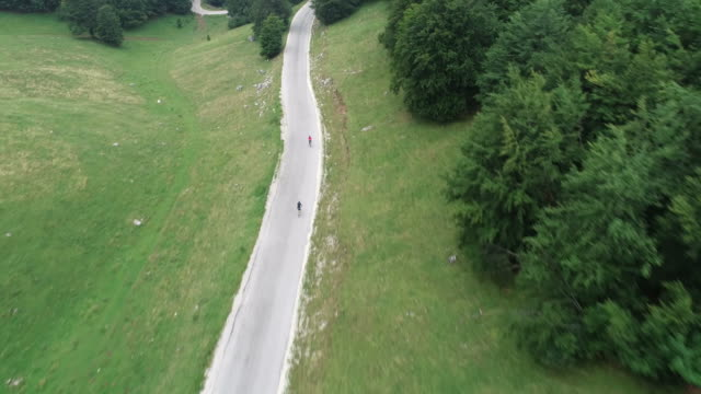 footage of two cyclists in the mountains riding their bikes down a road - triatleta video stock e b–roll