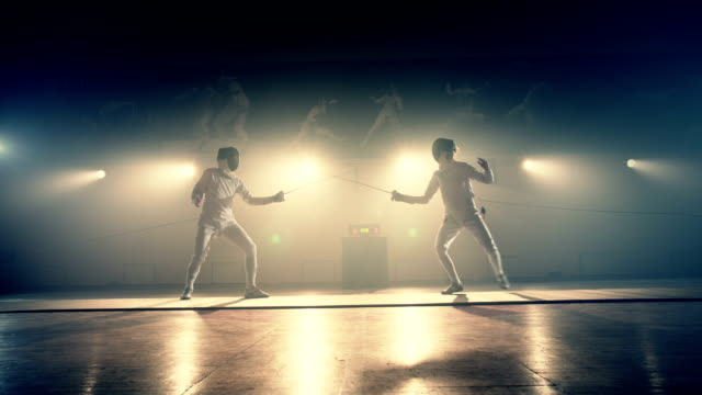 Footage of two fencing athletes duel . Two Professional Fencers Show Masterful Swordsmanship in their Foil Fight. Fencing training . Shot on ARRI ALEXA Cinema camera in slow motion