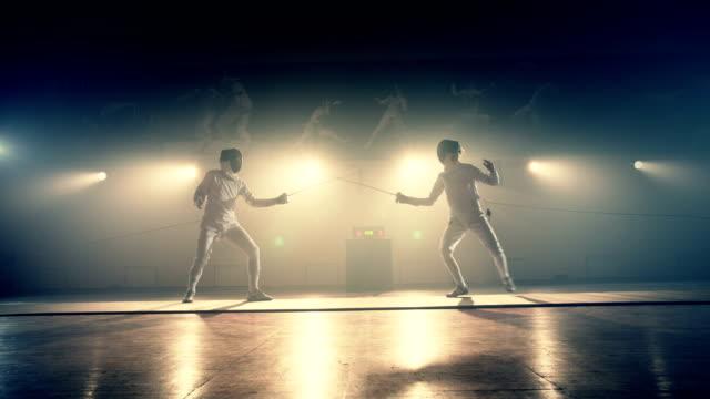 stockvideo's en b-roll-footage met beelden van twee schermen atleten duel . twee professionele schermers tonen meesterlijk zwaardvechten in hun foil fight. schermen opleiding . geschoten op arri alexa cinema camera in slow motion - fence