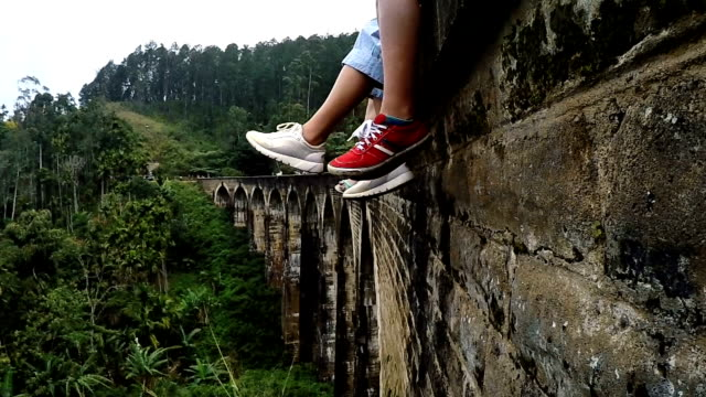 vídeos de stock e filmes b-roll de 4k footage of two people's feet in sport shoes dangling over valley. people sitting on stone viaduct in tropical forest. - sri lanka