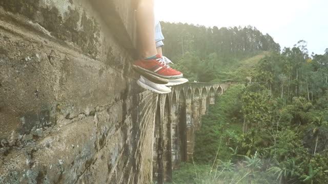 stockvideo's en b-roll-footage met 4k-beelden van twee mensen voeten in sportschoenen die over de vallei bungelen. mensen die op een stenen viaduct in tropisch bos zitten. - boog architectonisch element