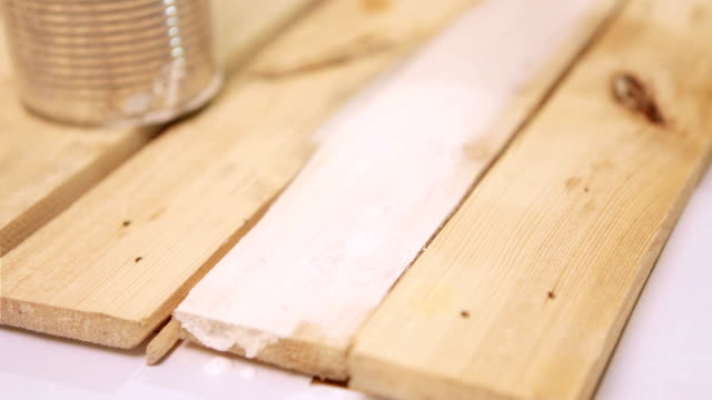 A footage of wooden boards being painted with white paint video
