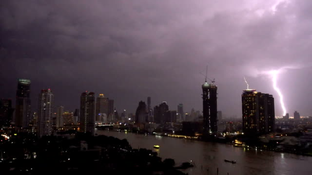 fhd footage scene of lightning with thunderstorm clouds at night over the bangkok cityscape river side, thailand, nature and cityscape concept - pioggia torrenziale video stock e b–roll