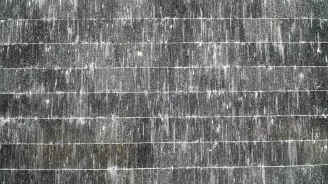 footage scene of modern water curtain close up with rock and brick wall