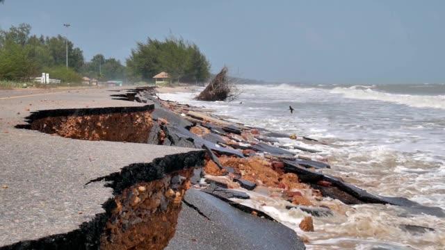 vídeos de stock, filmes e b-roll de ondas do mar filmagens, causadas por uma forte tempestade atingiu e destruir uma estrada de asfalto - erodido