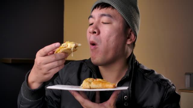 stockvideo's en b-roll-footage met 4k-beeldmateriaal tieners dragen winter kleding, hij eet pizza die belt om levering te bestellen - dikke pizza close up