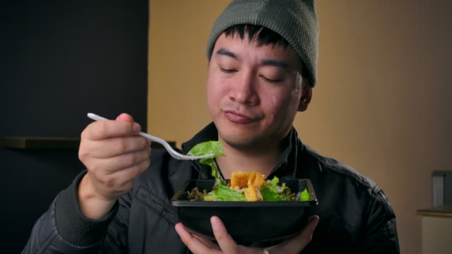 4K Footage Teenagers wear winter clothes, He is eating salad vegetables, And is a love for health.