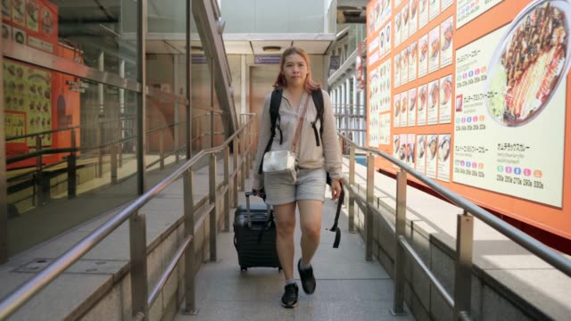 4K footage Women travellers walked in the link Between the train station and the airport.
