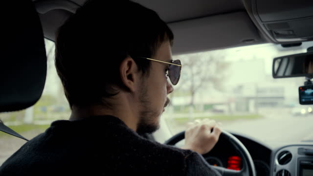 Footage young man behind the wheel. 4k