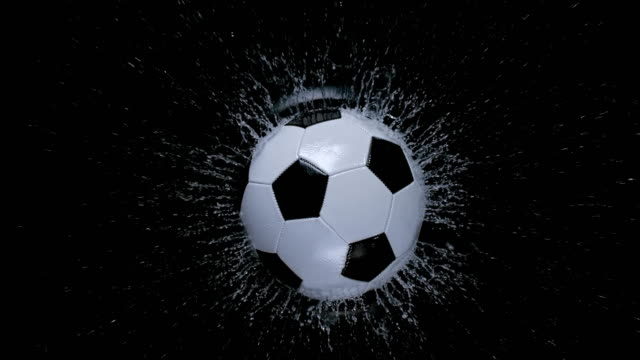 SLO MO LD Football falling into water on black background