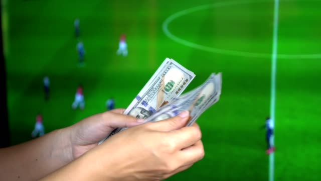 football gambling concept : hands counting money and give to another ones as if lose money. gambling soccer concept. tv screen showing football match as background. - gioco d'azzardo video stock e b–roll