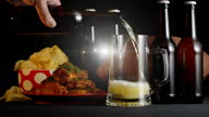istock Football party with male hand pouring beer into stein glass 1340345987