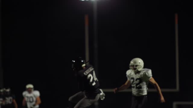 en fotbollsspelare nästan missar ett pass och sedan gör en touchdown och lägger på marken - fånga bildbanksvideor och videomaterial från bakom kulisserna