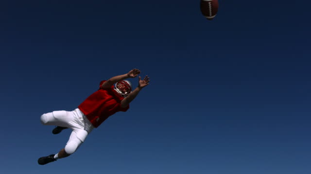 Football player catches ball, slow motion video