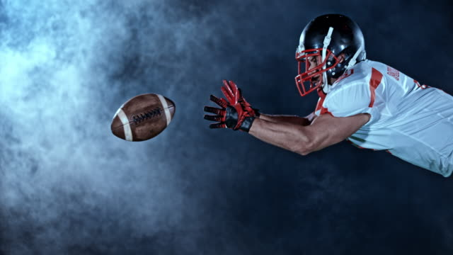 SLO MO LD Football player catching the ball in the air on the field at night video