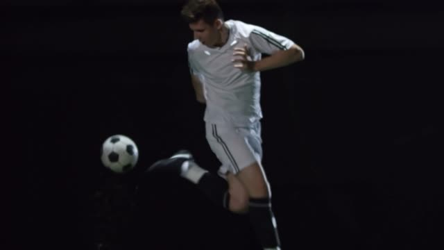 Football Player Dribbling Ball in Dark Arena video