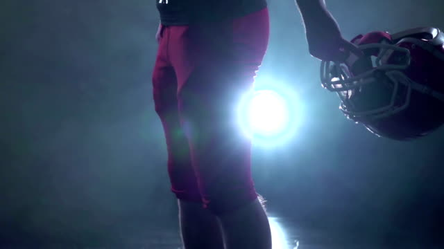 Football player holding a red protective helmet. Black background. Slow motion video