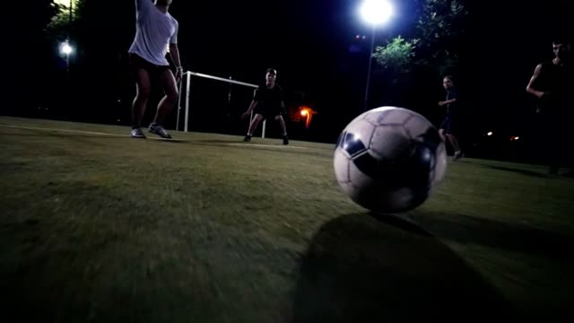 football player in white sneakers moves with the ball on the field, the other players attack, night shooting - grass isolated video stock e b–roll
