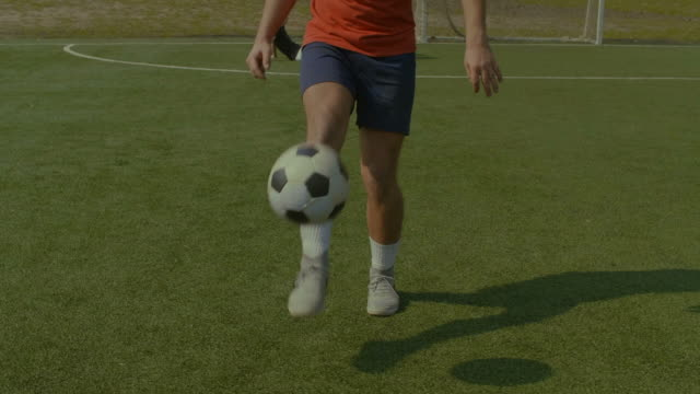 Football player juggling soccer ball on the pitch