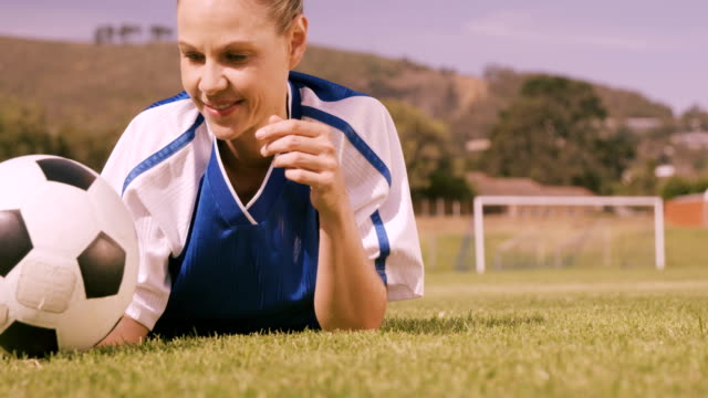 piłkarz leżący na pole z piłką - trykot filmów i materiałów b-roll