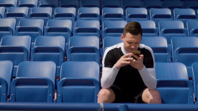 Football player on an empty tribune and looks into the phone