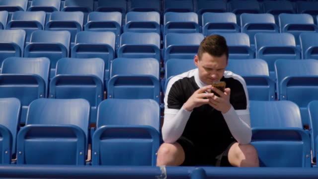 vídeos de stock e filmes b-roll de football player on an empty tribune and looks into the phone - adeptos