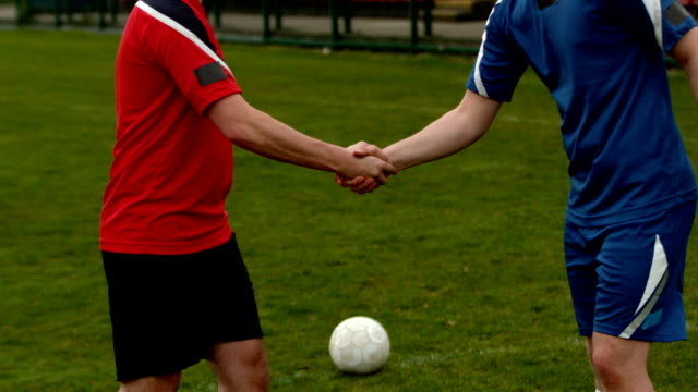 Football players shaking hands before a game Football players shaking hands before a game in slow motion rivalry stock videos & royalty-free footage