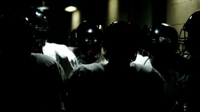 Football players walk through tunnel video