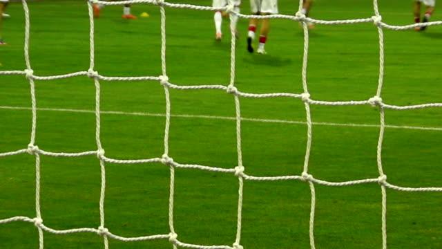 fußball-spieler zum aufwärmen – durch das netz - sportliga stock-videos und b-roll-filmmaterial