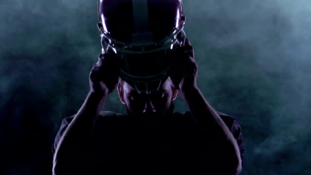 Football puts the helmet on the head in the smoke. Slow motion video