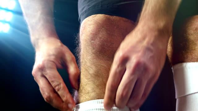 Football, soccer game. Professional footballer adjusting his socks, black background video