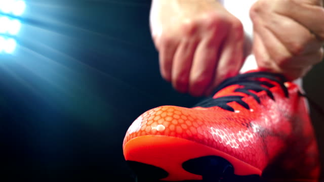 Football, soccer game. Professional footballer buckle his red shoes, black background video