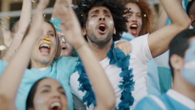 Football supporters in fan zone celebrating a goal Spectator in stadium celebrating victory their team's victory. Argentina football supporters cheering and jumping in unison at stadium. cheering stock videos & royalty-free footage