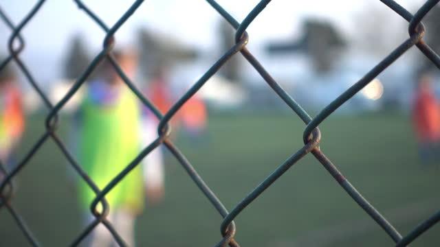Football Training Behind Metal Fence