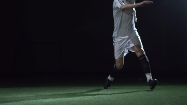 Footballer Shooting a Ball while Training in Dark Arena video