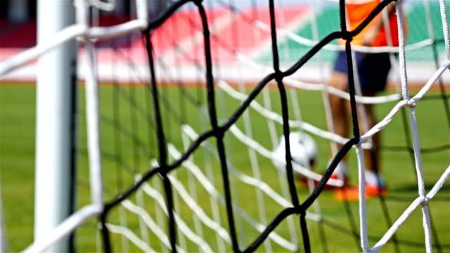 Footballer soccer player training, football net in front, 4k