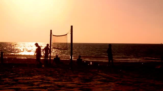 若い人々がフットバレーボールには、サンセットビーチ - サッカークラブ点の映像素材/bロール