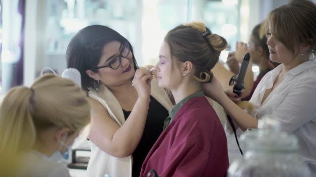 vidéos et rushes de jeune femme faisant de la coiffure, maquillage et manucure dans un salon de beauté - salons et coiffeurs