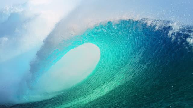 SLOW MOTION: Forceful barrel wave splashes water around the coast of Tahiti.