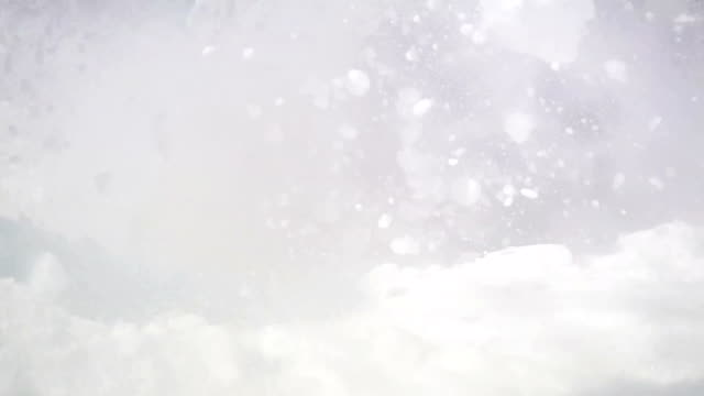 Forceful energetic dynamic footage of a skier going down the snowy slope with a moon on the blue sky. First real-time velocity video, then slows down to show the violent snowy burst. video