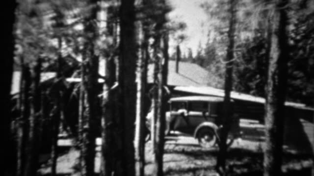 1934: Ford model A car driving past log cabin thru pine tree forest.