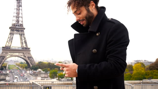 Foreign boyfriend chatting with French girl on smartphone around Eiffel Tower in slow motion video