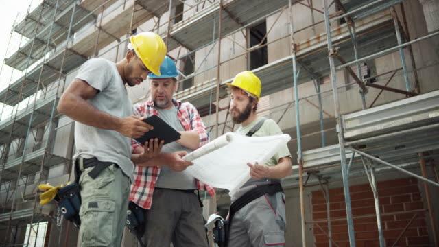förman och hans arbetare håller digital tabletten och planen och talar om tidslinjen - byggplats bildbanksvideor och videomaterial från bakom kulisserna