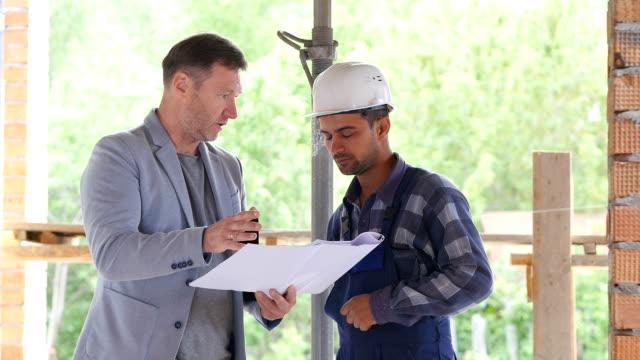 vídeos de stock e filmes b-roll de foreman scolds employee for bad work done - trabalho de design