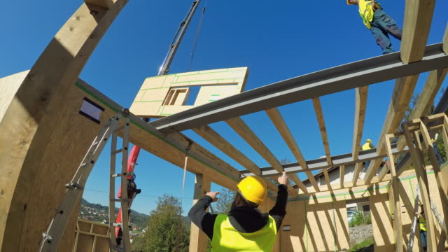 foreman signaling the worker operating the crane to move a wooden wall for the prefab home - industria edile video stock e b–roll