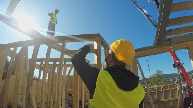 vídeos y material grabado en eventos de stock de foreman hablando a sus trabajadores en la construcción de una casa prefabricada - material de construcción