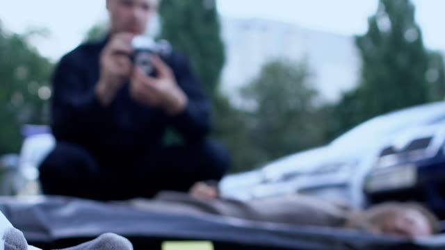судебно-медицинский эксперт, проводящий расследование на месте преступления, плюшевый мишка на асфальте - expert стоковые видео и кадры b-roll