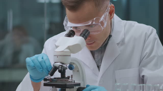 forensic expert man is researching analysis and evidences in laboratory, looking into microscope, exploring blood