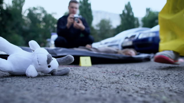 судебно-медицинский эксперт маркировки доказательств, полицейский делает фото жертвы, игрушка на дороге - expert стоковые видео и кадры b-roll