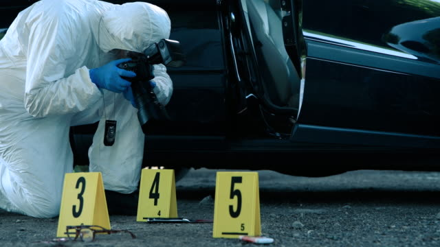 Forensic scientist working at crime scene Senior forensic scientist doing photographs at crime scene crime scene stock videos & royalty-free footage